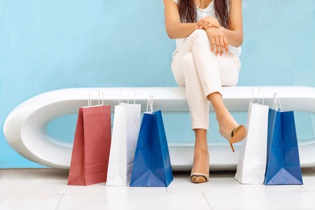 upbeat: Like shopping. Upbeat beautiful girl sitting on the bench and relaxing while being in the mall Stock Photo