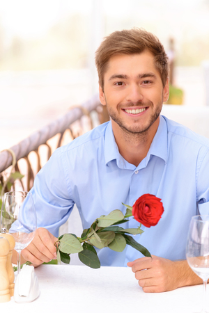to be pleasant: Be my lover. Pleasant delighted young man holding rose and sitting at the table while waiting for his girlfriend