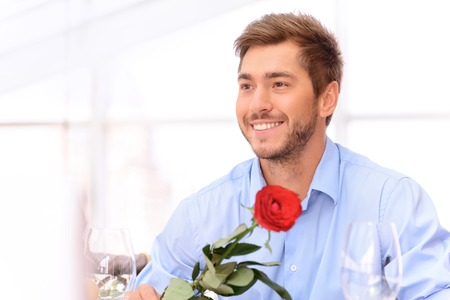 expressing joy: Happy to see you. Nice upbeat man holding rose and looking aside while expressing joy