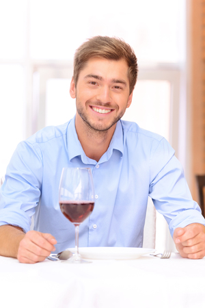 vivacious: Live fully. Pleasant vivacious young man sitting at the table and having dinner in restaurant while drinking wine