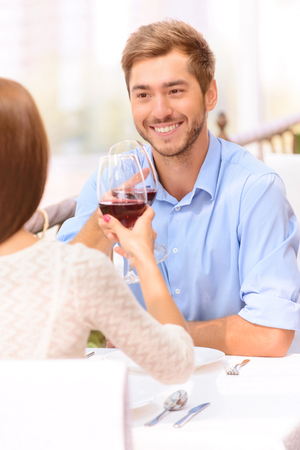 sublime: Sublime love. Nice vivacious man making toast and showing affection towards his love heart while drinking wine in the restaurant Stock Photo