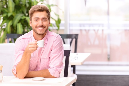 blissful: Life is unbelievable. Pleasant blissful handsome man drinking coffee and sitting at the table while relaxing in the cafe