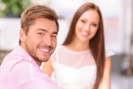 upbeat: Happy to be together. Selective focus of handsome upbeat man expressing gladness while resting with his wife