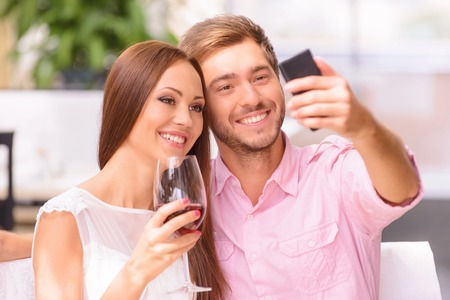say cheese: Say cheese. Nice contented beautiful couple making selfie and drinking wine while sitting in the cafe