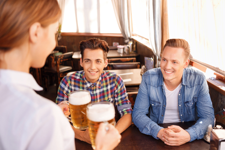 bringing: Best beverage. Pleasant handsome friends sitting at the table and looking at the waitress bringing them beer Stock Photo