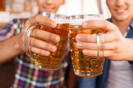 upbeat: Best beverage. Pleasant upbeat friend holding jugs of beer and going to drink it while relaxing in the pub Stock Photo
