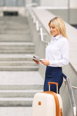upbeat: Real businesswoman. Pleasant attractive upbeat woman holding papers and leaning on the handrail while standing near office building