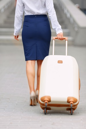 being the case: It is a nice journey. Pleasant attractive young woman holding suit case and going with it while being turned back