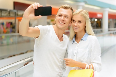 pleasant: Just smile. Pleasant handsome cheerful guy holding mobile phone and making selfie with his girl friend Stock Photo