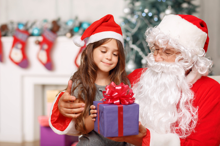 laugher: Happy childhood. Pleasant girl sitting with Santa Claus and holding present while expressing joy