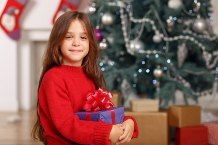 upbeat: Full of joy. Pretty upbeat little girl holding present and sitting near Christmas tree while expressing gladness