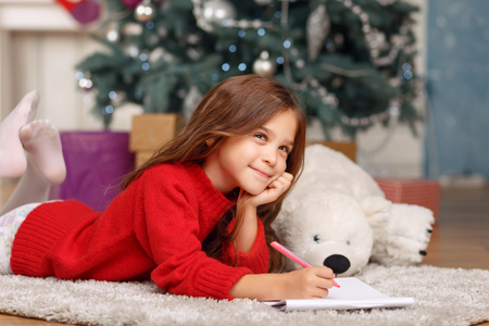 laugher: Good time. Pleasant thoughtful little girl holding pen and mulling over while lying on the carpet
