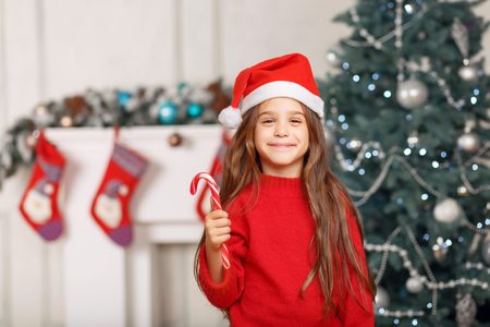 expressing joy: Favorite holiday. Overjoyed delighted little girl wearing hat and expressing joy and having fun near Christmas tree