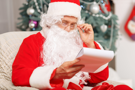 arm chair: Holiday preparation. Nice old Santa Claus sitting in the arm chair and making list of presents while expressing positivity Stock Photo