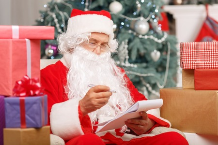 arm chair: Ready for holiday. Pleasant generous Santa holding pen and making list of presents while sitting in the arm chair
