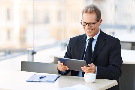 ejecutivo en oficina: Vivir con las tecnologías. Feliz vivaz apuesto hombre de negocios la celebración de ordenador portátil y sentado en la mesa al tiempo que expresa alegría Foto de archivo
