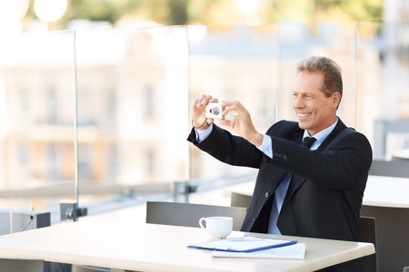upbeat: Just smile. Pleasant upbeat handsome businessman holding camera and sitting at the table while making photos