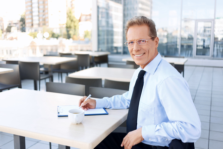 vivacious: Love my job. Pleasant vivacious handsome businessman holding pen and drinking coffee while sitting at the table Stock Photo