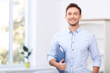 pleasant: Ready to sale. Pleasant cheerful handsome realtor holding folder and expressing positivity while standing near window Stock Photo