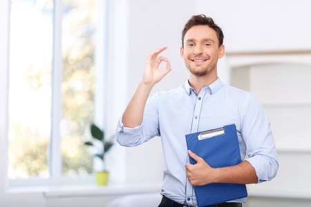upbeat: Everything is great. Nice upbeat handsome realtor holding folder and showing ok while going to sale Stock Photo