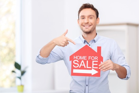 to be pleasant: Be with us. Pleasant cheerful handsome realtor holding the card and pointing it while feeling glad