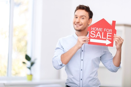 to be pleasant: Be a client of our company. Pleasant overjoyed handsome realtor holding card and expressing positivity Stock Photo