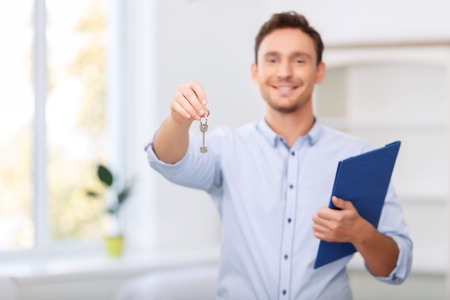 pleasant: Take it. Pleasant professional handsome realtor holding folder and giving you key while loving his job Stock Photo