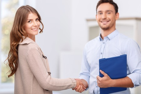 good service: Good service. Pleasant professional smiling realtor shaking hand of client while doing his job Stock Photo