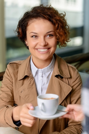 upbeat: Express energy. Cheerful pleasant upbeat young woman holding cup of coffee and expressing joy while sitting at the table
