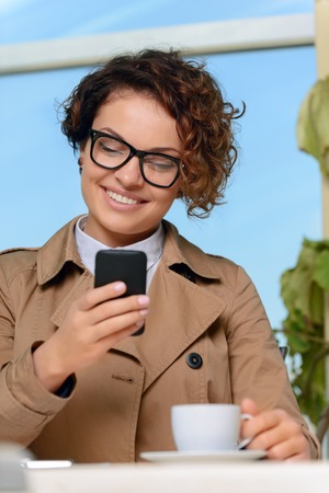 laugher: Be positive. Pleasant charming upbeat young woman holding mobile phone and drinking coffee while sitting at the table