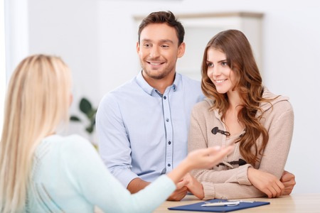 pleasant: Buying new flat. Pleasant loving young couple bonding to each other and speaking with professional realtor Stock Photo