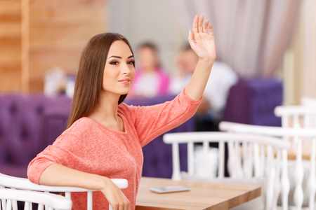 i am here: I am here. Pleasant cheerful appealing young girl holding her hand up and expressing joy while waiting in the cafe
