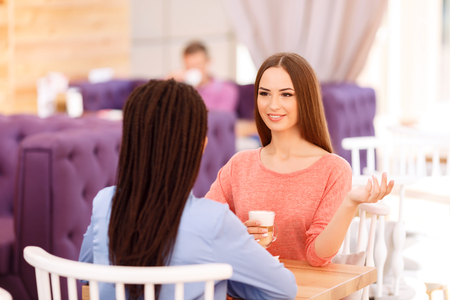 pleasant: Animated discussion. Pleasant contented girls sitting at the table and drinking coffee while having pleasant talk
