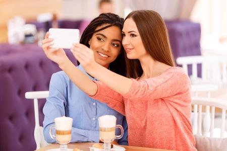 say cheese: Say cheese. Pleasant young beautiful girls sitting at the table and drinking coffee while making selfie Stock Photo