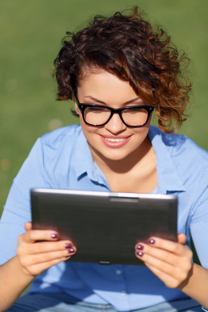 contented: Good news. Pretty appealing contented young girl holding laptop and expressing joy while having rest on the grass Stock Photo