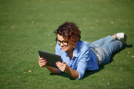 contented: Happy weekend. Contented cheerful smiling young girl lying on the grass and holding laptop while spending great time