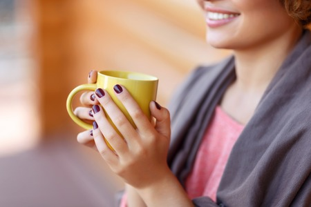 relive: Best way to relive stress. Close up of yellow cup in hands of young girl holding it and reveling in drinking tea