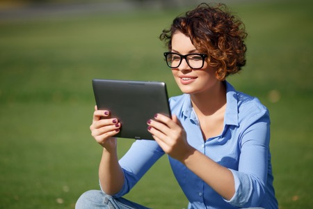 contented: Modern girl . Pleasant attractive contented girl holding laptop anf looking at it while relaxing outdoor Stock Photo