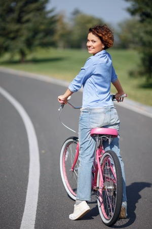 vivacious: Enjoy my life. Overjoyed pleasant smiling vivacious girl holding bicycle and going to ride while standing on the road Stock Photo