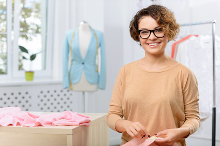 designer at work: Nice fabric. Positive upbeat smiling designer holding cloth and sawing it while making clothes