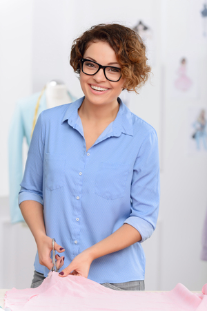 upbeat: Full of energy. Pleasant contented upbeat designer holding scissors and cutting the fabric while making clothes