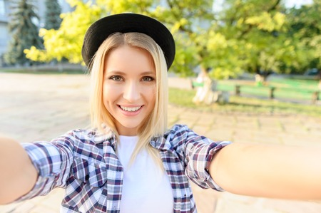 girl face close up: Young and beautiful. Elated pretty girl making selfie while having a walk around the city Stock Photo