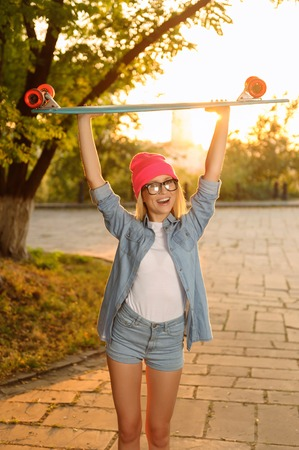 blissful: Full of happiness. Cheerful agreeable vivacious girl keeping her hands up and holding skateboard in them while filling blissful Stock Photo