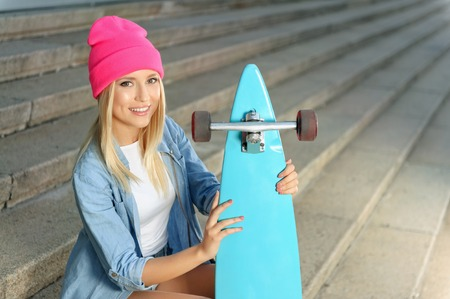 expressing joy: It is my hobby. Nice smiling beautiful girl holding skateboard and sitting on the footsteps while expressing joy