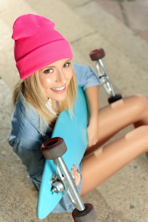 tightly: Like doing it. Top view of cheerful delighted attractive active young girl holding tightly her skateboard and sitting on the footsteps while relaxing