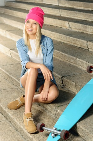agreeable: Active way of life. Agreeable vivacious charming delighted young lady sitting on the footsteps near her skateboard while resting