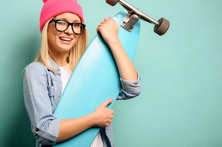 upbeat: Skate with me. Pleasant upbeat content young girl holding skateboard and smiling while standing isolated on blue background