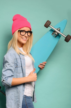 agreeable: Life is good. Agreeable smiling upbeat girl holding skateboard and thumbing up while standing isolated on blue background