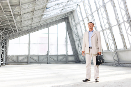 upbeat: Qualified specialist. Positive handsome upbeat architect holding case and looking up while working