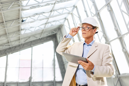 agreeable: Make the progress. Professional agreeable architect keeping his glasses and holding laptop while looking up